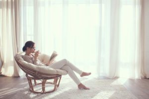 Woman sitting in white room reading a book from