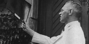 Black and white photograph of Dr. Max Gerson looking at an x-ray, from