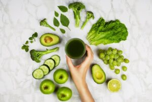 "Photo of green vegetables and fruits with hand holding green juice from ""Mums' Magical Antiviral Hot LemonAid Tonic"" by Green Smoothie Girl"