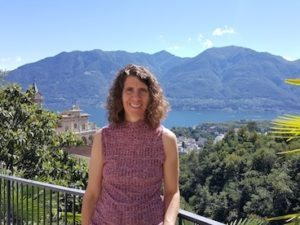 Happy lady on sunny balcony overlooking lush valley