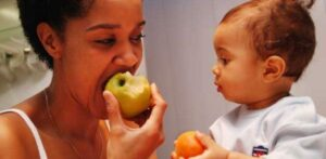 "Photograph of a mother and baby, each holding a piece of fruit, from ""9 Ways to Get Your Kids to Drink Healthy Green Smoothies"" at Green Smoothie Girl."