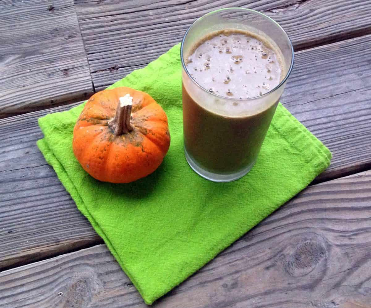 Photograph of a smoothie and a small pumpkin on a green napkin.