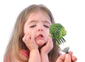 Does everything that goes in your mouth have to TASTE good? A young girl makes a face when confronted with eating broccoli.