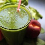 """Photo of green smoothie in glass with pink straw and peaches from """"Easiest Starter Green Smoothie"""" recipe by Green Smoothie Girl"""