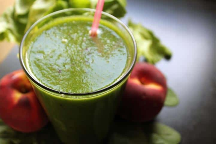 "Photo of green smoothie in glass with pink straw and peaches from ""Easiest Starter Green Smoothie"" recipe by Green Smoothie Girl"