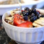 """picture of a smoothie with granola, blueberries, strawberries, and bananas in a white bowl on a counter from """"Acai Smoothie Bowl"""" by Green Smoothie Girl"""