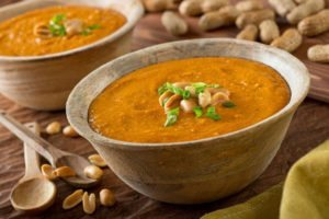 a delicious bowl of homemade african peanut soup with green onion garnish from