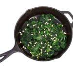 Photo of sauteed spinach and pine nuts in skillet from