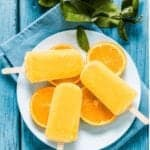 "Photo of orange popsicles on top of orange slices and white place from ""Orange Dreamsicle Popsicle"" recipe by Green Smoothie Girl"