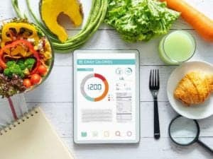 Photo of food surrounding tablet with calorie counter app displayed from