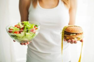 Photo of woman holding salad in one hand and cheeseburger with measuring tape in the other from