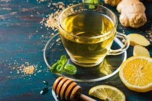 "Photo of lemon tea in glass cup with cut lemons honey and ginger surrounding from ""Immune-Fuel Hot LemonAid""recipe by Green Smoothie Girl"