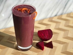 """Photo of a pink smoothie topped with carrot spirals next to a cut beet from Green Smoothie Girl's """"hot pink smoothie"""""""