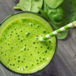 "Photo of topdown view of green smoothie with green striped paper straw in it and spinach surrounding from ""{VIDEO} Why Are You Afraid of Detoxing?"" by Green Smoothie Girl"