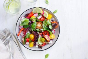 "Photo of colorful salad in white bowl on white background from ""Could Toxicity Be Why I'm Sick? (7 Types of Toxins In Your Body)"" by Green Smoothie Girl"