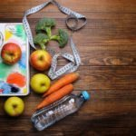 "Photo of water bottle, apples, carrots, broccoli, scale, soft measuring tape on wooden background from ""{VIDEO} How to Change Your Weight ""Set Point"" Forever"" by Green Smoothie Girl"