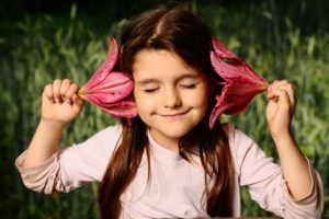 "Image of a young girl holding flowers by her ears, from ""Which Natural Treatments for ADHD Symptoms Are Backed by Science?"""