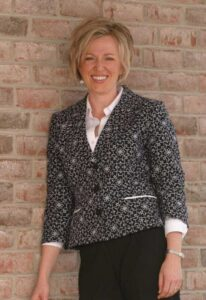 Photo of Dr. Jorgensen leaning against brick wall and smiling from