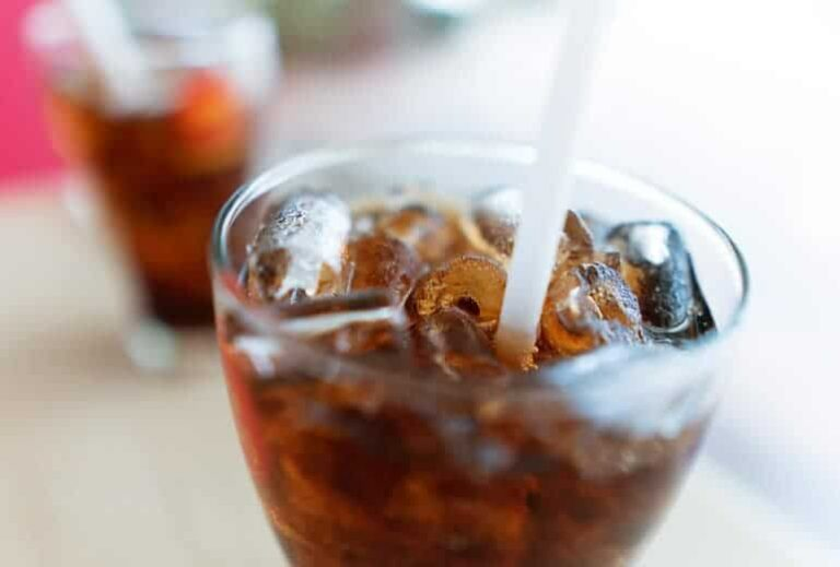 "Photo of brown soda with straw and ice from ""Can Soda Dissolve Teeth? The Worst Drinks For Dental Health"" by Green Smoothie Girl"