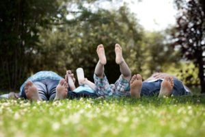 "A family laying on the grass together from ""{VIDEO} How to ""Ground"" and ""Charge"" for High Energy Every Day!"" by Green Smoothie Girl"