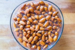 "Photo of bowl of soaking almonds from ""13 Top Raw Almonds Nutrition Benefits (And How To Get Truly Raw Almonds)"" by Green Smoothie Girl"