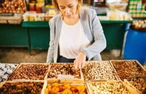 "Photo of a woman choosing almonds in a grocery store nut display from ""13 Top Raw Almonds Nutrition Benefits (And How To Get Truly Raw Almonds)"" by Green Smoothie Girl"