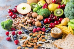 "Photo of fruits, vegetables, and nuts spilling on table from ""What Are Probiotics Benefits? 11 Signs You're Deficient And What To Do About It"" by Green Smoothie Girl"