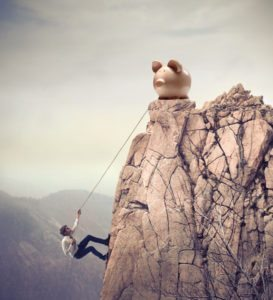 Young businessman scaling a rock to reach a large payoff
