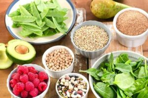 Image of a table full of foods like berries, nuts, avocado, and grains, from