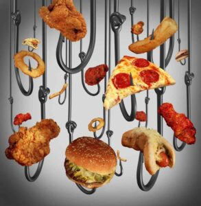 Eating addiction health care concept with a group of hooks using fast food as human bait as fried chicken hamburgers and french fries as a symbol of the dangers of being hooked on sugar fat and salt.
