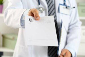 Image of a Doctor handing a patient a prescription