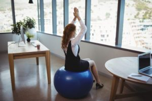 Executive exercising on fitness ball in office