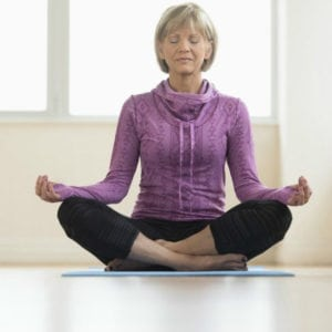 Photo of mature woman sitting in a meditation post from