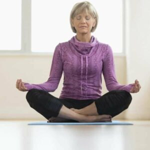 Image of mature woman with eyes closed sitting in lotus position at home. Blog: Herxheimer Reaction: What Is It, How Do I Clear It?