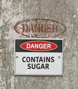 red, black and white Danger, Contains Sugar warning sign. Blog: How to Beat Your Sugar Addiction in Four Days.