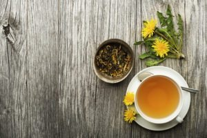 Cup of healthy dandelion tea on wooden background. Blog: Detoxifying Drinks Review: What Works? What Doesn't?