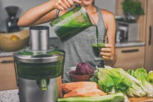 Woman juicing making green juice with juice machine in home kitchen.