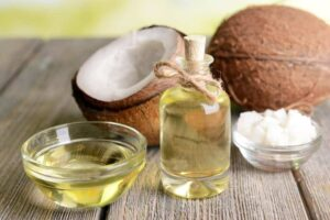 Photo of open coconut with jar of coconut oil from