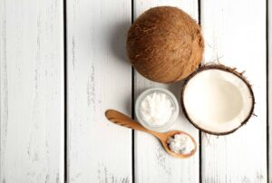 Coconut oil is legendary for its numerous health benefits. Photograph of whole coconuts and solid coconut oil.