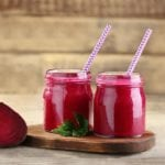 "Photo of two pink smoothies in glass jar with striped straws and cut beet on the side from ""Hot Pink Smoothie"" recipe by Green Smoothie Girl"