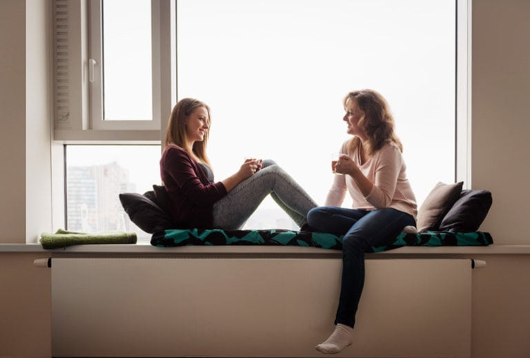 "Photograph of a mother and teenage daughter talking in front of a window, from ""9 Ways to Get Kids to Drink Healthy Green Smoothies"" at Green Smoothie Girl."
