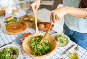 "Image of someone tossing a salad in a wooden bowl, from ""Which Natural Treatments for ADHD Symptoms Are Backed by Science?"" at Green Smoothie Girl."