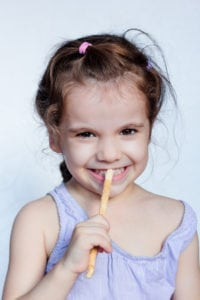 "Photo of young girl using a Miswak toothbrush from ""Miswak Toothbrush: Why You Should Use a Stick to Brush Your Teeth"" by Green Smoothie Girl"