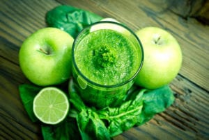 "Photograph of a green smoothie in a glass surrounded by apples, limes, and leafy greens, from ""9 Ways to Get Kids to Drink Healthy Green Smoothies"""