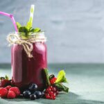 Photo of purple smoothie in glass jar with straws, berries surrounding