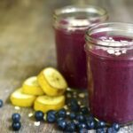 """Photo of purple smoothie in glass jars with bananas and blueberries next to it from """"Oatmeal Breakfast Smoothie"""" recipe by Green Smoothie Girl"""