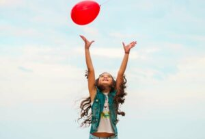 "Image of a young girl jumping for a red balloon, from ""Which Natural Treatments for ADHD Symptoms Are Backed by Science?"""