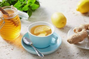 "Photograph of a cup of hot honey lemon tea with fresh ginger root, from ""Top Proven Ginger Health Benefits and My Favorite Ways to Use It"" at Green Smoothie Girl"