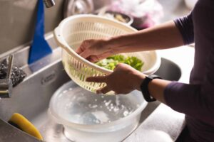 "Photograph of a person washing vegetables in a kitchen sink, from ""How To Freeze Spinach and Other Leafy Greens For Later (With Shortcuts!)"" at Green Smoothie Girl."
