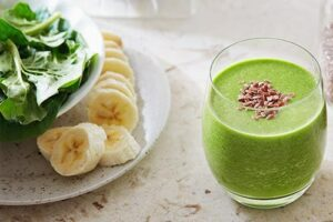"Photograph of a green smoothie in a small glass, next to a plate of salad and bananas, from ""10 Easy Green Smoothies Kids Will Love"""